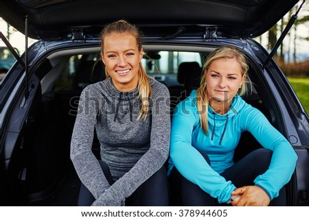 two beautiful young girls preparing for run in back of car, smiling and laughing - stock photo