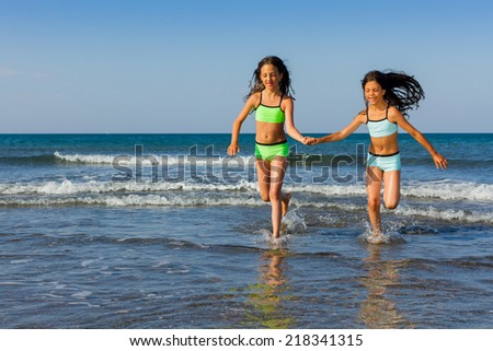 Two beautiful young girls running on the beach