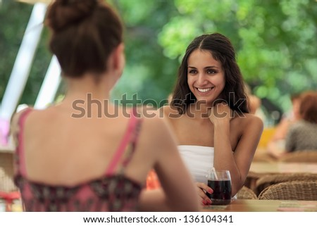 Two beautiful young girls sitting by the table in cafe and talki - stock photo