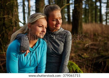 two beautiful young girls sitting on log arms around watching sunset - stock photo