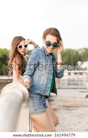 two beautiful young girls stand by river handrail and smile - stock photo