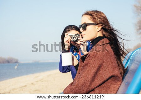 Two beautiful young girls taking pictures on an old camera on the beach on a sunny day. Outdoor, lifestyle - stock photo
