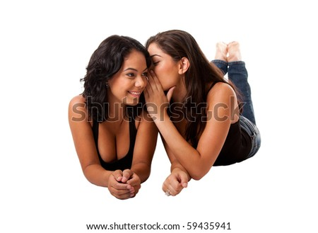 Two beautiful young happy women laying, sharing telling a gossip secret, isolated.
