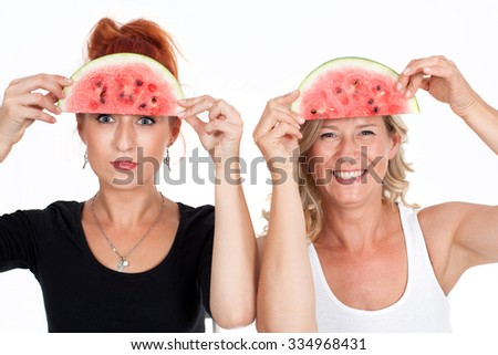 Two beautiful young healthy, happy woman with blond hair and red-haired smiling while holding a watermelon in his hands. pranks, jokes, fun, joy, Nutrition, diet, nutrition - stock photo