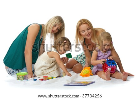 Two beautiful young mother with her daughters lying on the floor and play with toys