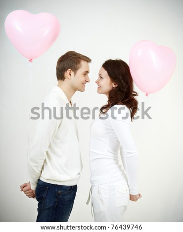 Two beautiful young people with heart-shaped balloons looking at each other - stock photo
