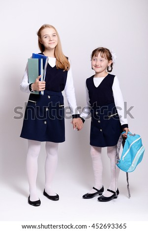 Two Beautiful young school girl advertises school uniforms.Isolated studio portrait