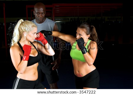 Two beautiful young woman fighters working with their trainer in an MMA gym - stock photo