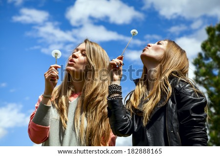 Two beautiful young woman in the forest are blowing on dandelions on background blue sky - stock photo