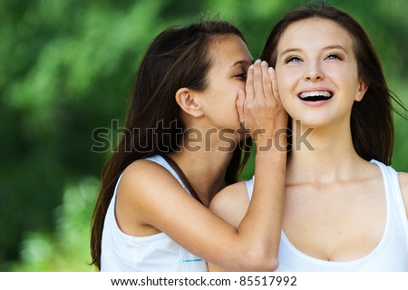 two beautiful young woman long dark hair whispering secret - stock photo
