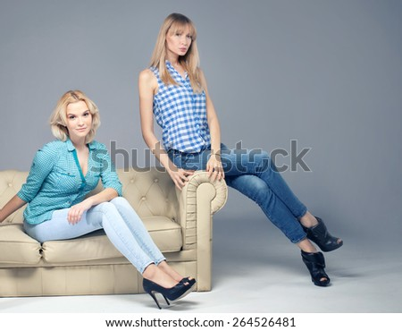 Two beautiful young woman posing in fashionable jeans, looking at camera. Blonde girls. Studio photo. - stock photo