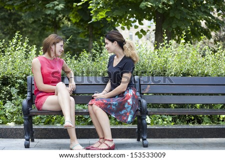 Two beautiful young woman resting on a bench in the park - stock photo