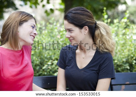 Two beautiful young woman resting on a bench in the park