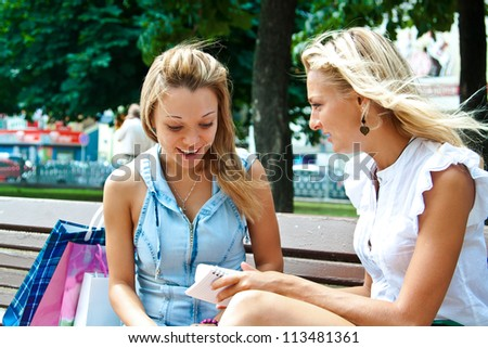 Two beautiful young woman resting on a bench in the park after shopping - stock photo
