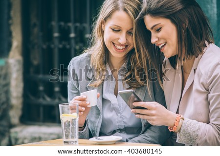 Two beautiful young woman sitting at cafe drinking coffee and looking at mobile phone - stock photo