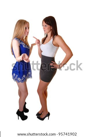 Two beautiful young woman standing in the studio arguing with another, one blond and the other one brunette in short dresses, over white. - stock photo