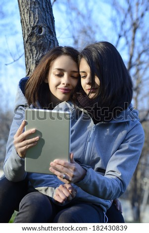 Two beautiful young women browsing a tablet outside while sitting on a tree - stock photo
