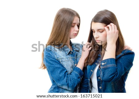 Two beautiful young women comforting one another on white background - stock photo