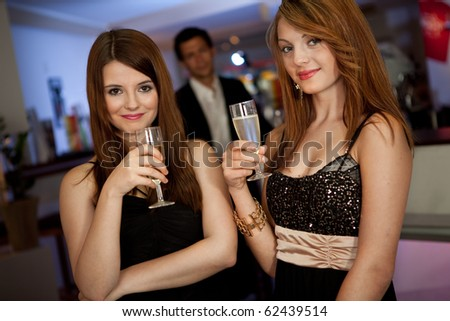 Two beautiful young women drinking chanpagne - stock photo