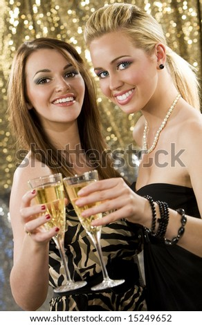 Two beautiful young women enjoying champagne in a nightclub - stock photo