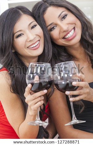 Two beautiful young women friends, Asian Chinese and Hispanic having fun drinking red wine together - stock photo