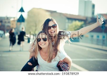 two beautiful young women having fun in the city - stock photo