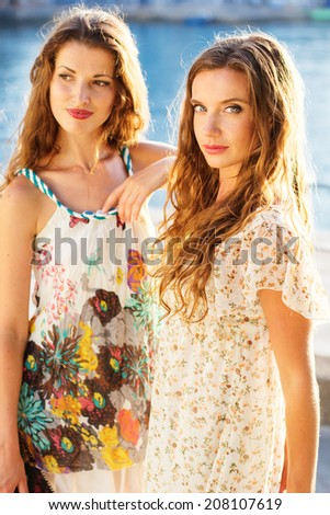 Two beautiful young women having fun in the city - stock photo