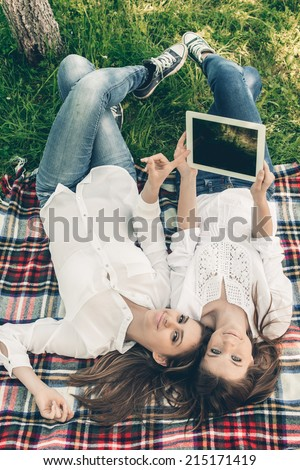 Two beautiful young women having fun while browsing a tablet out - stock photo