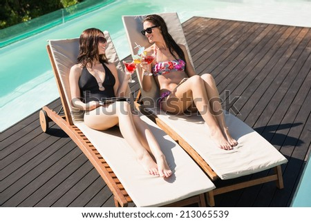 Two beautiful young women holding drinks by swimming pool - stock photo