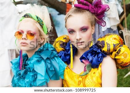 Two beautiful young women in a garden. Outdoors - stock photo