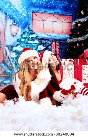 Two beautiful young women in Christmas clothes posing over Christmas background. - stock photo