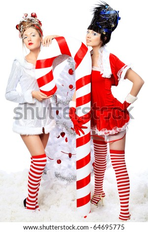 Two beautiful young women in Christmas clothes posing with a big candy. - stock photo