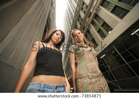 Two beautiful young women in New York City street. Wide angle. - stock photo