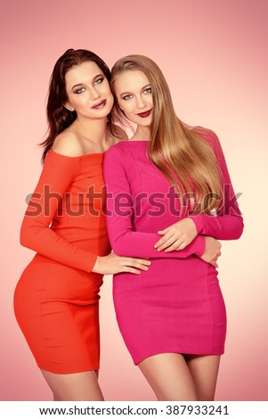 Two beautiful young women in red dresses posing together. Beauty, fashion. - stock photo