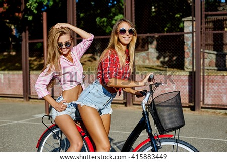 Two beautiful young women in sunglasses riding bicycle in summertime - stock photo