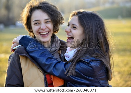 Two beautiful young women laughing and having fun outside in a park