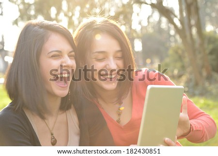 Two beautiful young women laughing and having fun while browsing a tablet - stock photo