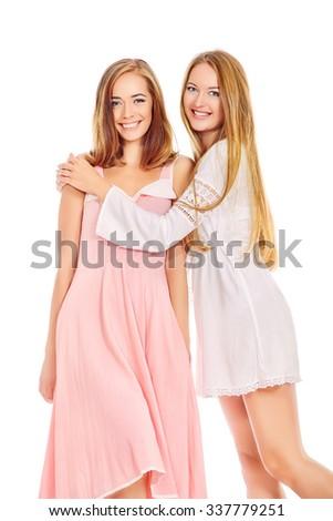 Two beautiful young women posing at studio in light summer dresses. Beauty, fashion. - stock photo