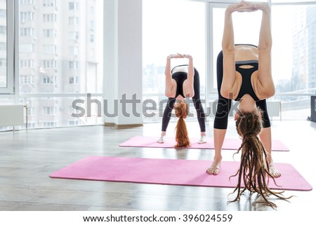 Two beautiful young women practicing yoga in studio - stock photo