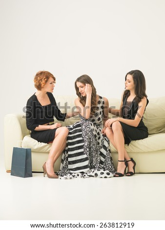 two beautiful young women sitting on sofa, comforting another while she worries not having money to buy a dress - stock photo