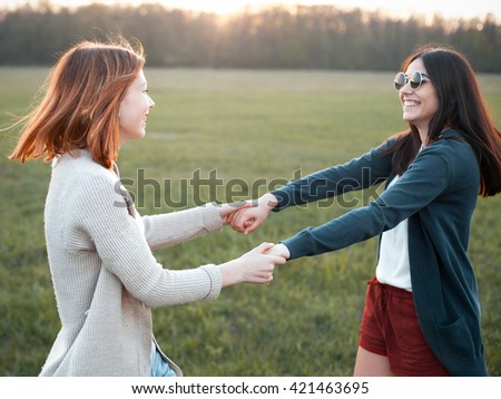 Two beautiful young women smiling and dancing in the sunset. Best friends - stock photo