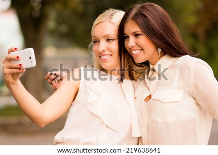 Two beautiful young women taking pictures of themselves on the phone. Two girls blond and brunette smiling and doing selfie - stock photo