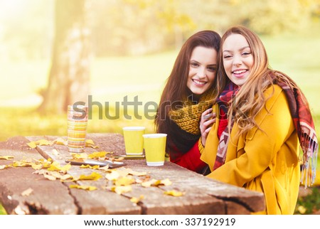 Two beautiful young women talking and enjoying on a sunny autumn day  - stock photo