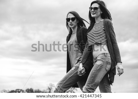 Two beautiful young women walking under a cloudy sky. Black and white - stock photo