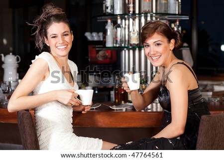 Two beautiful young women with great smile and hairstyle sitting at a bar, drinking coffee. - stock photo