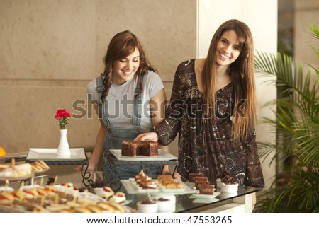 Two beautiful young women with great teeth enjoying a dessert buffet, smiling to the camera, palm tree in the background. - stock photo