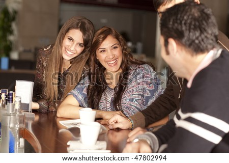 Two beautiful young women with great teeth enjoying their lunch break, sitting at a bar, flirting, drinking coffee, smiling - stock photo