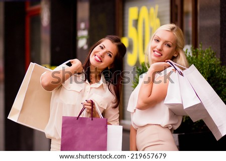 Two beautiful young women with shopping bags smiling, standing outside the shop. Overstock, cheerful shopping - stock photo
