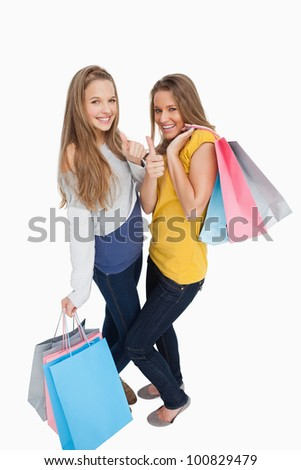Two beautiful young women with shopping bags the thumb-up against white background - stock photo