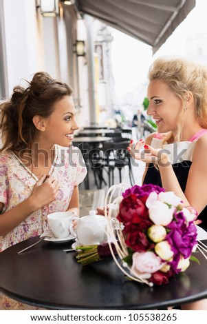 Two beautiful young women with smile and hairstyle sitting at a bar, drinking tea and coffee. - stock photo